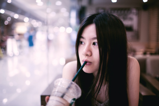 Portrait of young girl drinking coffee in cafe