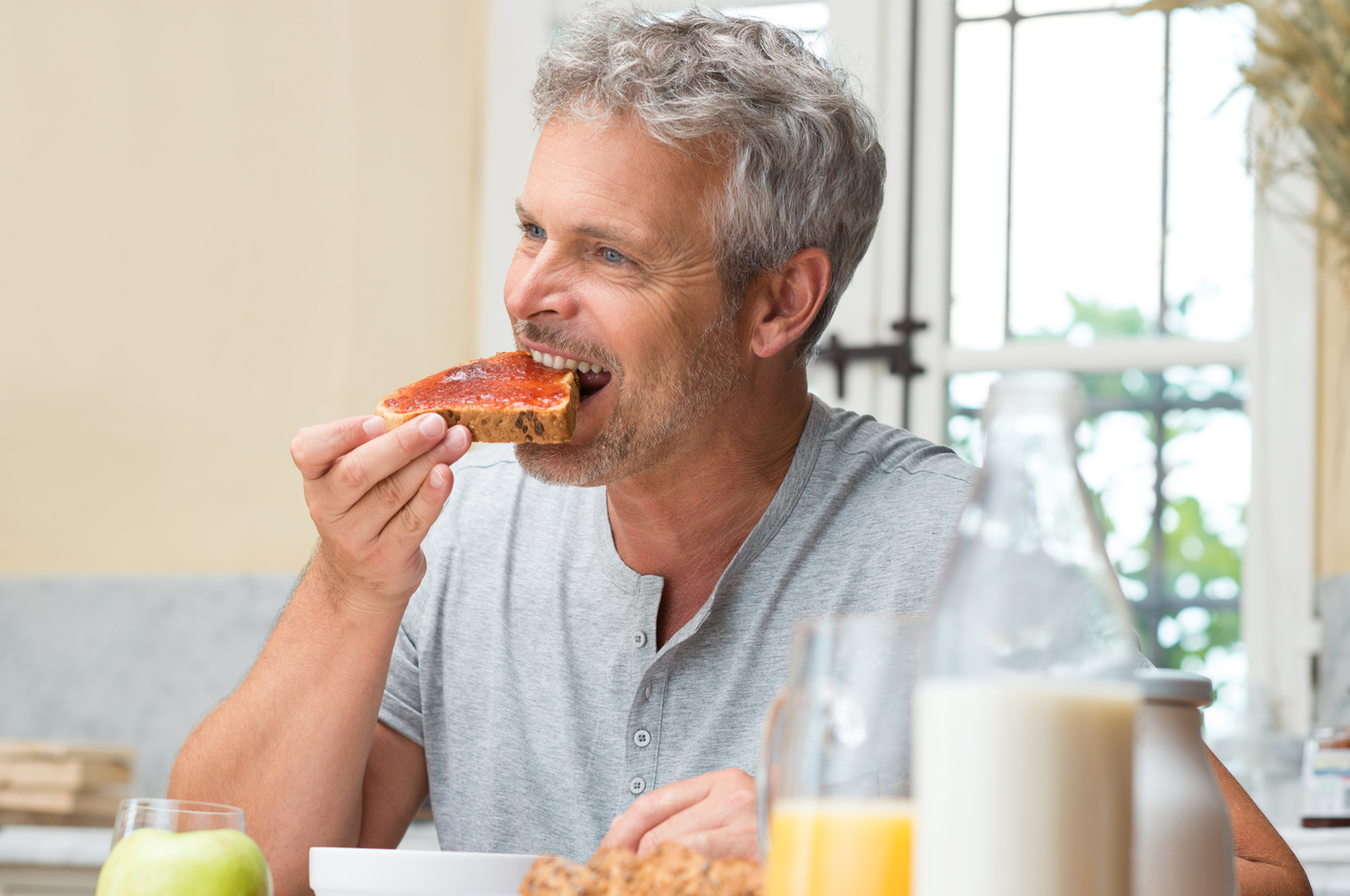 Mature Man Eating A Fresh Slice Of Bread With Jam For Breakfast